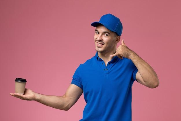 Widok z przodu męski kurier w niebieskim mundurze uśmiechnięty i trzymający dostarczającą filiżankę kawy na różowej ścianie, jednolita dostawa pracy serwisowej