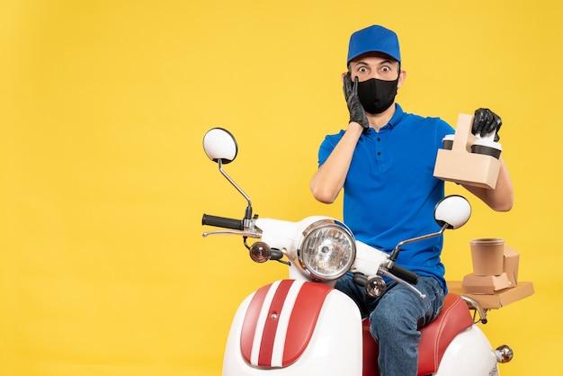 Widok z przodu męski kurier w niebieskim mundurze z kawą na żółtym rowerze pandemicznym covid - usługa pracy wirusa dostarczania pracy