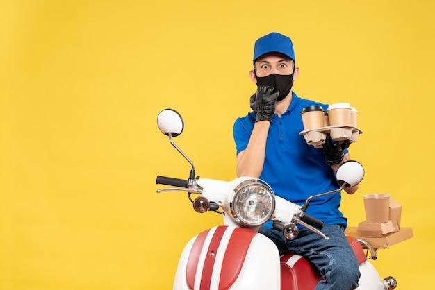 Widok z przodu męski kurier w niebieskim mundurze z kawą na żółtym rowerze praca covid - wirus pandemiczny usługi dostarczania pracy