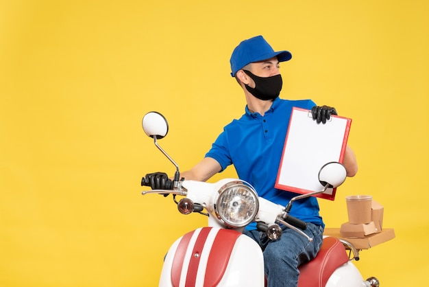 Widok z przodu męski kurier w niebieskim mundurze z notatką na żółtym rowerze praca covid - usługa dostarczania wirusa pracy