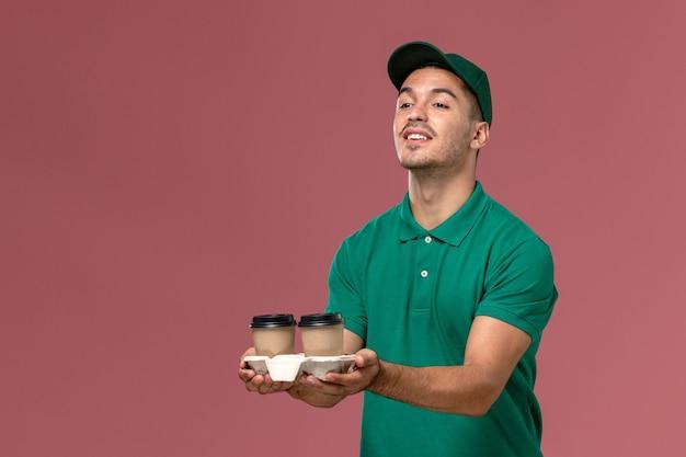 Widok z przodu męski kurier w zielonym mundurze dostarczający filiżanki z kawą na jasnoróżowym tle