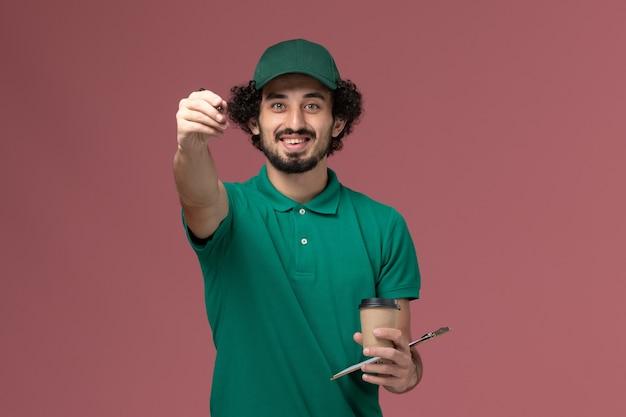 Widok z przodu męski kurier w zielonym mundurze i pelerynie trzymający dostawczą filiżankę kawy z notatnikiem i długopisem na różowym biurku jednolita usługa dostawy praca w firmie