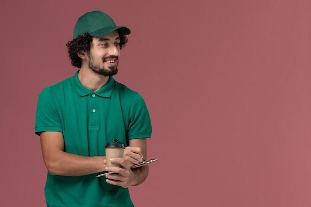 Widok z przodu męski kurier w zielonym mundurze i pelerynie trzymający dostawczą filiżankę kawy z notatnikiem i długopisem na różowym tle jednolita usługa dostawy praca w firmie