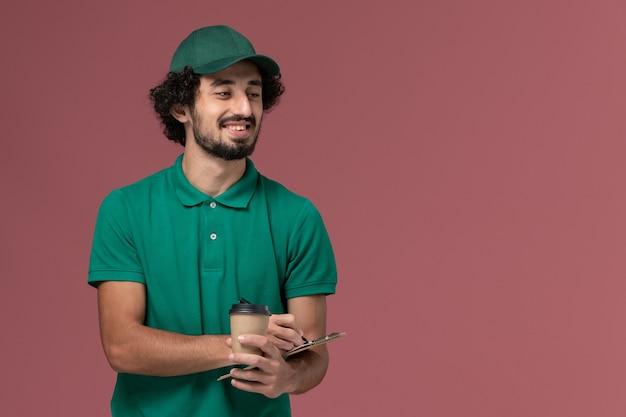 Widok z przodu męski kurier w zielonym mundurze i pelerynie trzymający dostawczą filiżankę kawy z notatnikiem i długopisem uśmiechnięty na różowym tle jednolita usługa dostawy praca w firmie