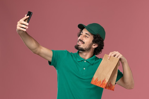 Widok z przodu męski kurier w zielonym mundurze i pelerynie trzymający paczkę z jedzeniem i rozmawiający przez telefon na różowej podłodze usługa mundurowa dostawa męska praca