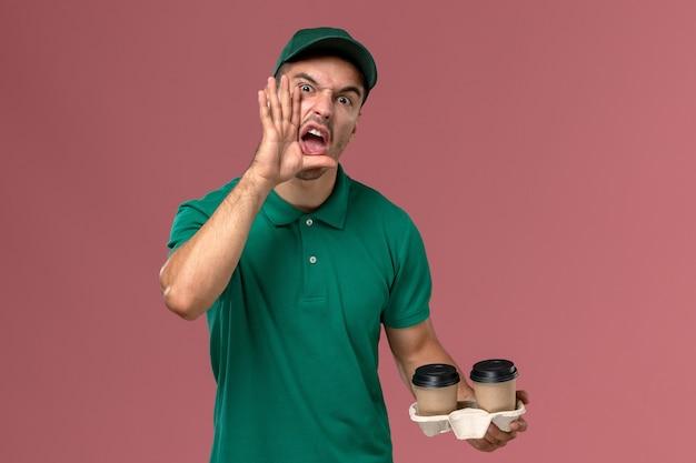 Widok z przodu męski kurier w zielonym mundurze krzyczący i trzymający brązowe filiżanki kawy na różowym tle