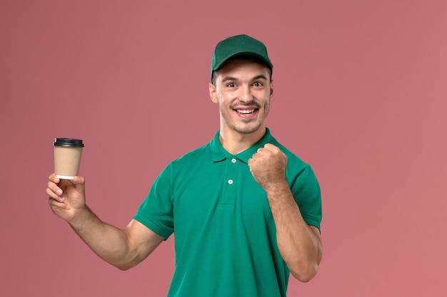 Widok z przodu męski kurier w zielonym mundurze raduje się i trzyma filiżankę kawy na różowym tle