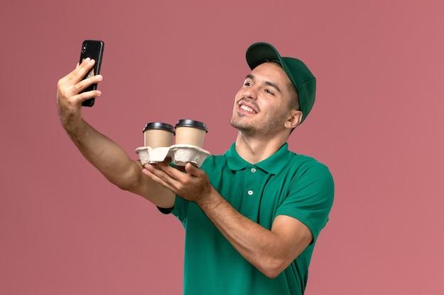 Widok z przodu męski kurier w zielonym mundurze robiący zdjęcie z kawą na różowym tle