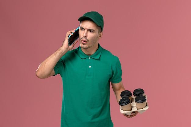 Widok z przodu męski kurier w zielonym mundurze, trzymając brązowe filiżanki kawy podczas rozmowy przez telefon na różowym biurku