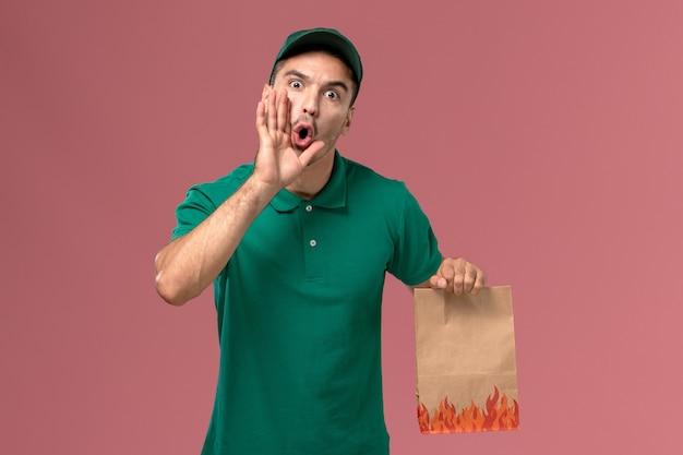 Widok z przodu męski kurier w zielonym mundurze, trzymając papierowy pakiet żywności na jasnoróżowym tle