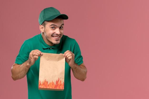 Widok z przodu męski kurier w zielonym mundurze, trzymając papierowy pakiet żywności z uśmiechem na różowym tle