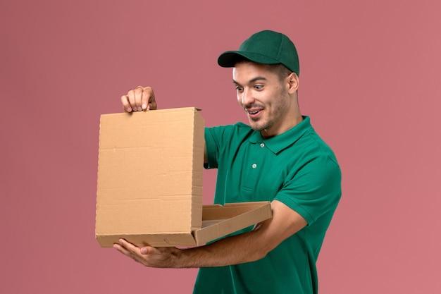 Widok z przodu męski kurier w zielonym mundurze, trzymając pudełko z jedzeniem i otwierając je na różowym tle