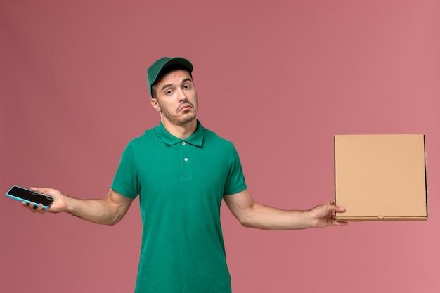 Widok z przodu męski kurier w zielonym mundurze, trzymając pudełko z jedzeniem i telefon na różowym tle