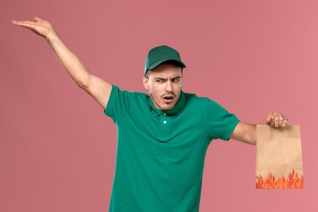 Widok z przodu męski kurier w zielonym mundurze, trzymający paczkę z jedzeniem z zmieszanym wyrazem twarzy na jasnoróżowym tle