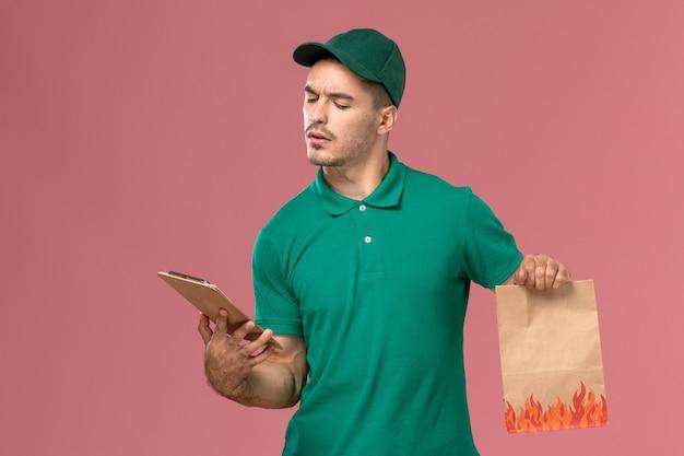 Widok z przodu męski kurier w zielonym mundurze trzymający pakiet żywności i notatnik na jasnoróżowym tle