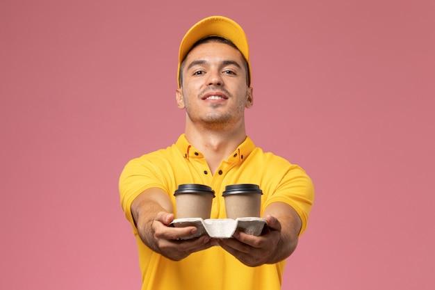 Widok z przodu męski kurier w żółtym mundurze dostarczający filiżanki kawy dostawy na różowym tle