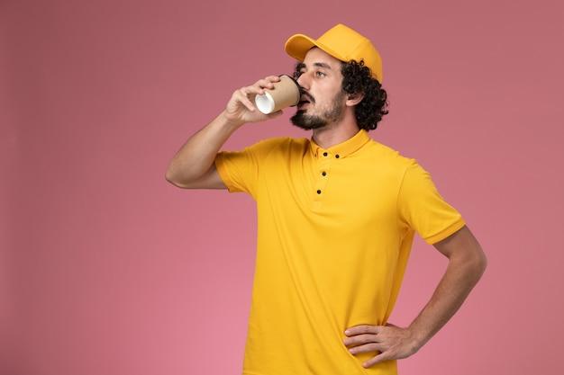 Widok z przodu męski kurier w żółtym mundurze i pelerynie pijący kawę na różowej ścianie