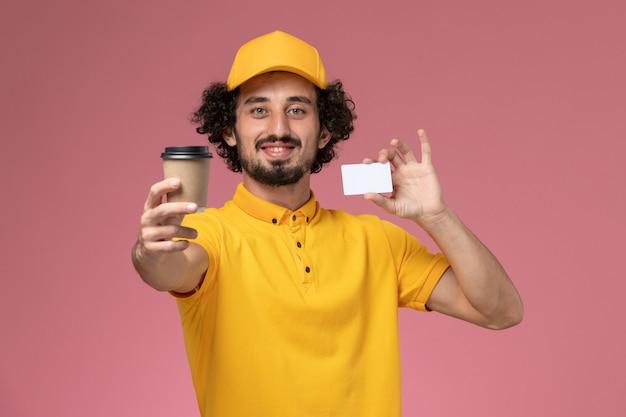 Widok z przodu męski kurier w żółtym mundurze i pelerynie, trzymając filiżankę kawy dostawy i kartę na różowej ścianie