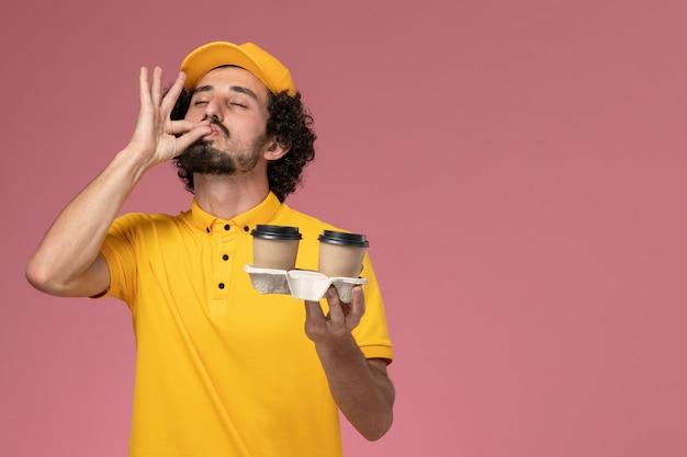 Widok z przodu męski kurier w żółtym mundurze i pelerynie, trzymając filiżanki kawy dostawy pozowanie na różowej ścianie