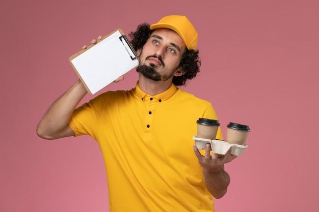 Widok z przodu męski kurier w żółtym mundurze i pelerynie trzymający brązowe filiżanki z kawą i notatnik na różowej ścianie