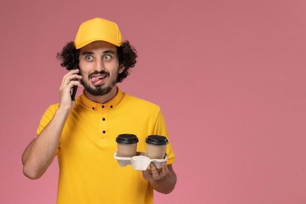 Widok z przodu męski kurier w żółtym mundurze i pelerynie trzymający brązowe kubki dostawy kawy rozmawiający przez telefon na różowej ścianie
