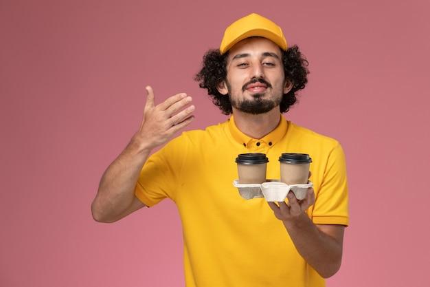 Widok z przodu męski kurier w żółtym mundurze i pelerynie trzymający dostawcze filiżanki kawy pachnące na różowej ścianie