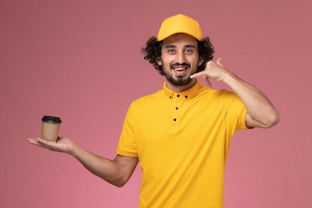 Widok z przodu męski kurier w żółtym mundurze i pelerynie trzymający filiżankę kawy dostawy na różowej ścianie
