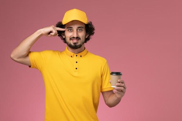Widok z przodu męski kurier w żółtym mundurze i pelerynie trzymający filiżankę kawy na jasnoróżowej ścianie