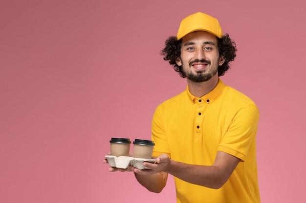 Widok z przodu męski kurier w żółtym mundurze i pelerynie trzymający filiżanki kawy dostawy na różowej ścianie