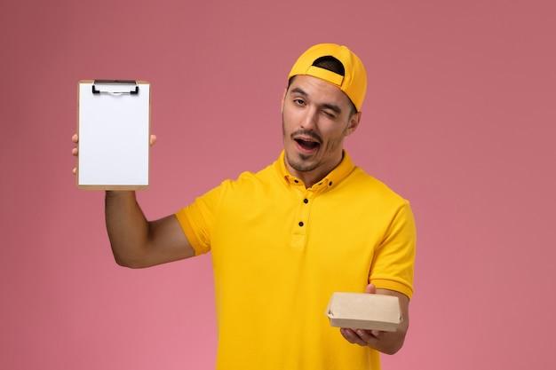 Widok z przodu męski kurier w żółtym mundurze i pelerynie trzymający małą paczkę z dostawą żywności i mrugający notatnik na różowym tle.