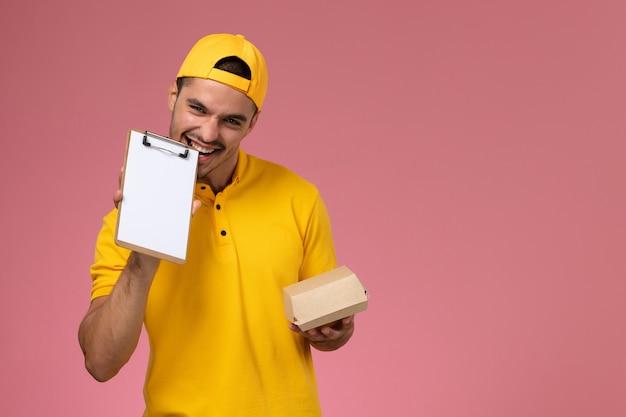 Widok z przodu męski kurier w żółtym mundurze i pelerynie trzymający małą paczkę z dostawą żywności i notatnik na różowym biurku.