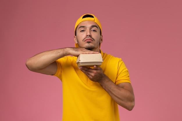 Widok z przodu męski kurier w żółtym mundurze i pelerynie trzymający małą paczkę z dostawą żywności na jasnoróżowym tle.