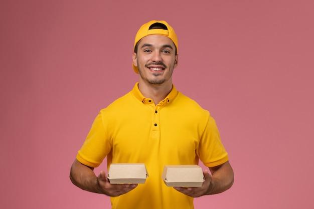 Widok z przodu męski kurier w żółtym mundurze i pelerynie trzymający małe opakowania żywności dostawy na różowym tle.