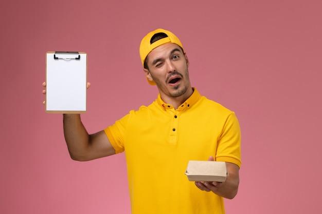 Widok z przodu męski kurier w żółtym mundurze i pelerynie trzymający niewielki notatnik dostawy żywności na różowym tle.