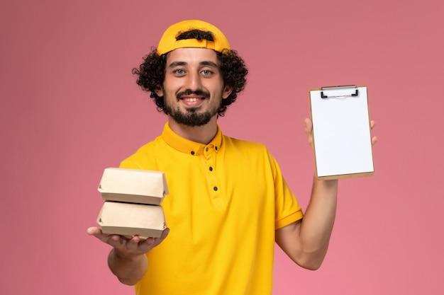 Widok z przodu męski kurier w żółtym mundurze i pelerynie z małymi paczkami z dostawą żywności i notatnikiem na rękach na jasnoróżowym tle.