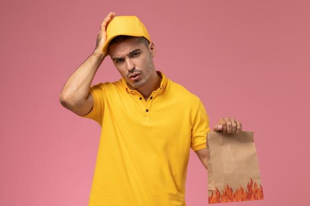 Widok z przodu męski kurier w żółtym mundurze, mający ból głowy i trzymający pakiet żywności na różowym tle