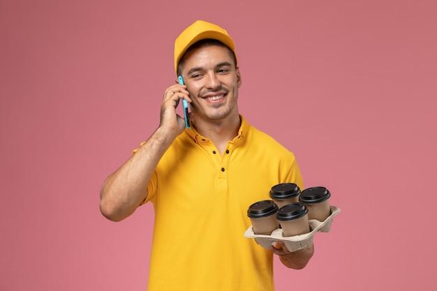 Widok z przodu męski kurier w żółtym mundurze, trzymając filiżanki kawy dostawy i rozmawiający przez telefon z uśmiechem na różowym biurku
