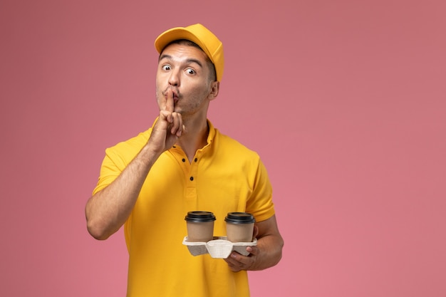 Widok z przodu męski kurier w żółtym mundurze, trzymając filiżanki kawy dostawy prosząc o ciszę na jasnoróżowym tle