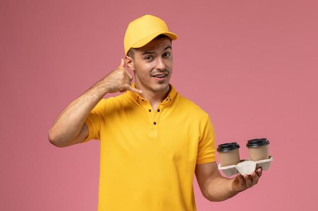 Widok z przodu męski kurier w żółtym mundurze, trzymając filiżanki kawy dostawy rozmowa telefoniczna pozowanie na jasnoróżowym tle