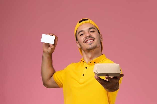 Widok z przodu męski kurier w żółtym mundurze trzymając kartę i mały pakiet żywności na różowym tle.