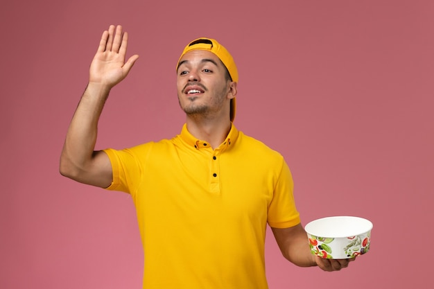 Widok z przodu męski kurier w żółtym mundurze, trzymając miskę dostawy i machając na jasnoróżowym tle.