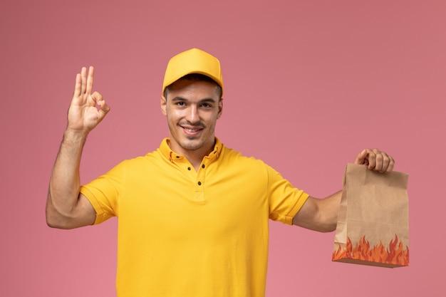 Widok z przodu męski kurier w żółtym mundurze, trzymając pakiet żywności z uśmiechem na różowym tle
