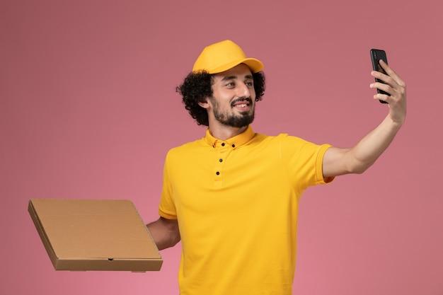 Widok z przodu męski kurier w żółtym mundurze, trzymając pudełko dostawy żywności, biorąc zdjęcie na różowej ścianie