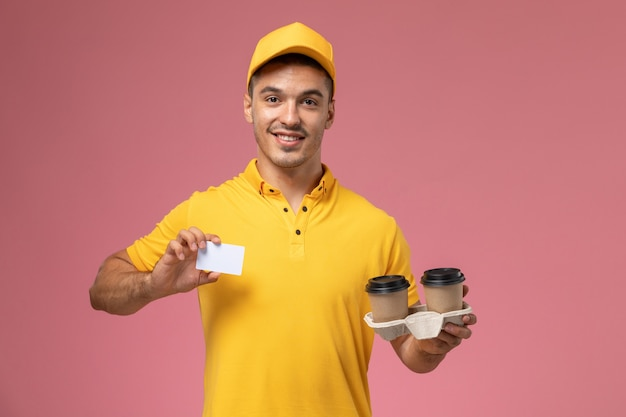 Widok z przodu męski kurier w żółtym mundurze, trzymając szarą kartę i filiżanki kawy dostawy na różowym tle