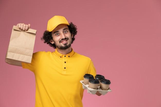 Widok z przodu męski kurier w żółtym mundurze, trzymający brązowe filiżanki do kawy i opakowanie żywności na różowej ścianie