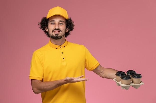 Widok z przodu męski kurier w żółtym mundurze trzymający brązowe filiżanki kawy dostawy na różowej ścianie