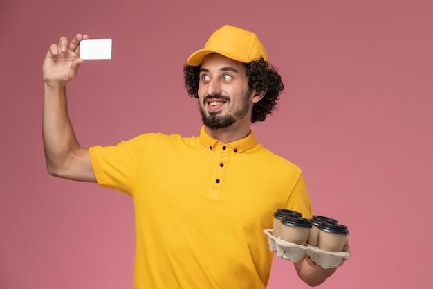 Widok z przodu męski kurier w żółtym mundurze, trzymający brązowe filiżanki z kawą i białą kartkę na różowej ścianie