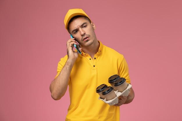 Widok z przodu męski kurier w żółtym mundurze trzymający dostawy filiżanek kawy i rozmawiający przez telefon na różowym biurku