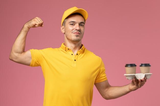 Widok z przodu męski kurier w żółtym mundurze, trzymający filiżanki kawy dostawy i zginający się na jasnoróżowym tle