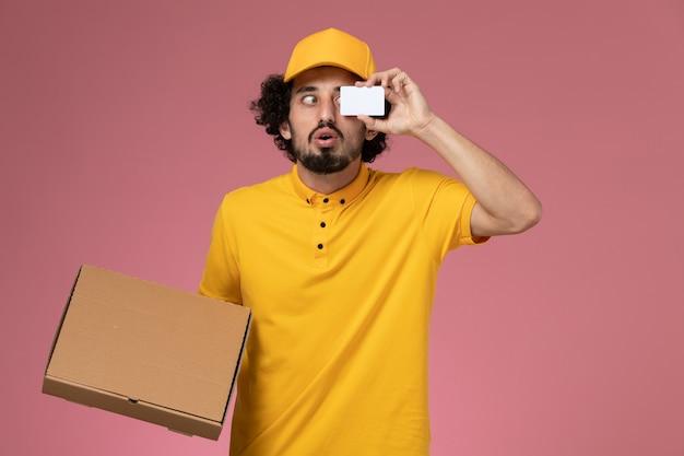 Widok z przodu męski kurier w żółtym mundurze, trzymający pudełko z dostawą żywności i kartę na jasnej ścianie